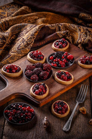 Tartlets with fresh red berries on wooden background Foto de archivo