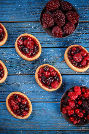 Tartlets with fresh red berries on blue wooden background
