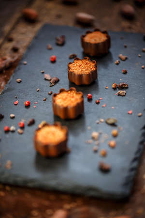 Fine chocolate pralines filled with marzipan decorated with crushed pink pepper served on black slate Archivio Fotografico