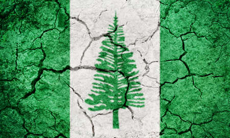 Norfolk Island flag on dry earth ground texture background Stock Photo
