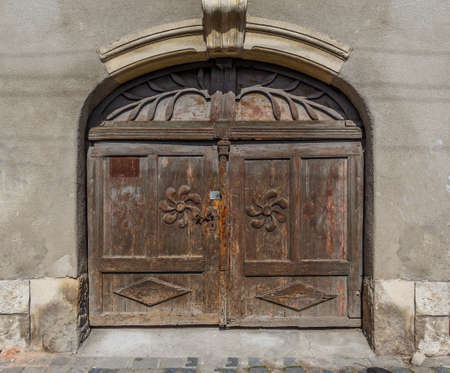 Very old, worn closed wooden door with ornaments