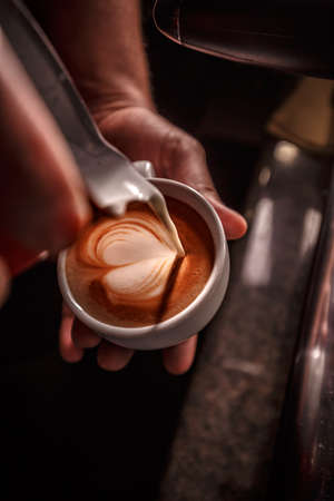 Barista pouring milk for prepare cup of coffee, latte art, Coffee preparation and service concept Stock Photo