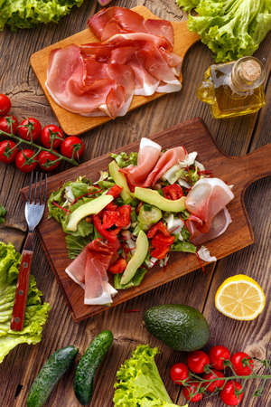 Mix of salad with smoked ham and vegetables on wooden cutting board