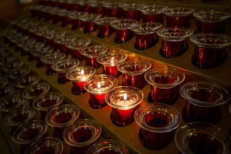 Burning candles in church, rows of candle Stock Photo