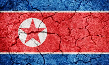 Democratic People's Republic of Korea flag on dry earth ground texture background Foto de archivo