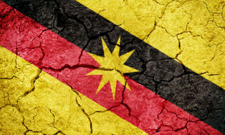 Sarawak, state of Malaysia, flag on dry earth ground texture background