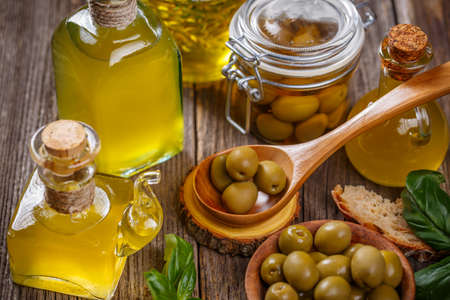 Bottles of extra virgin olive oil and olive berries