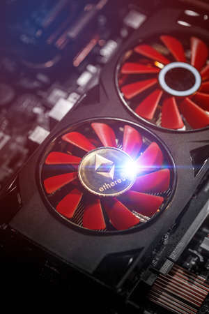 Ethereum and video card, close-up. Cryptocurrency mining concept with golden ethereum Stock Photo
