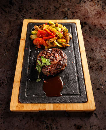 Matured Argentinian ribeye steak with grilled vegetables and barbecue sauce Stock Photo