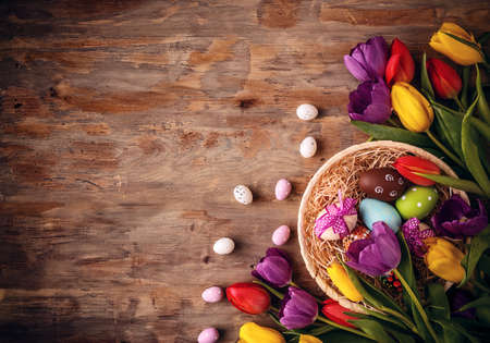 Easter eggs in basket with tulips on old wooden background Stock Photo