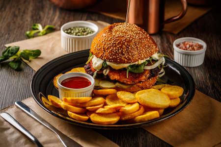 American burger with fried potatoes on the dark plate Фото со стока