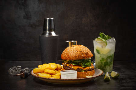Dinner with burger and glass of mojito cocktailon dark background