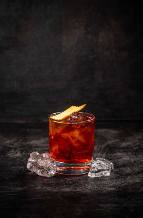 Negroni cocktail decorated with orange peel on dark background 免版税图像