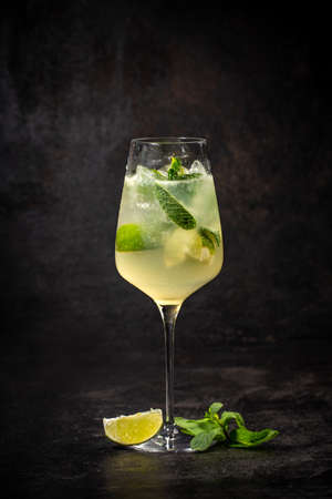 Cocktail with ice and lime on black background