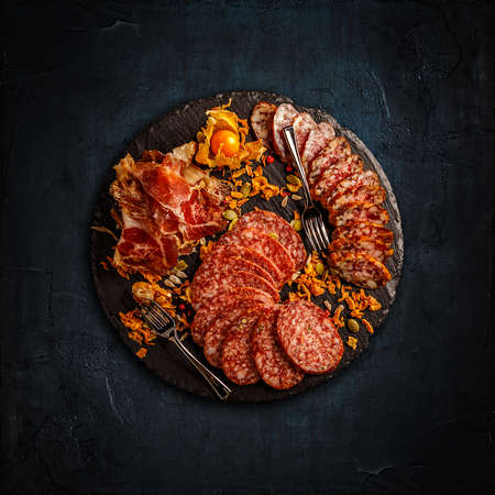 Slate board with prosciutto, salami and sausages on dark background