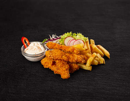 Crispy fried chicken breast strips with french fries and garlic sauce
