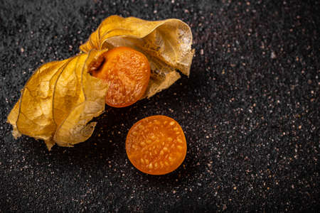 Physalis peruviana fruit cut in half on black background
