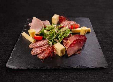 Meat delicatessen board on black slate