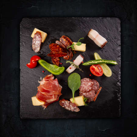 Slate board with prosciutto, salami, fat and sausages