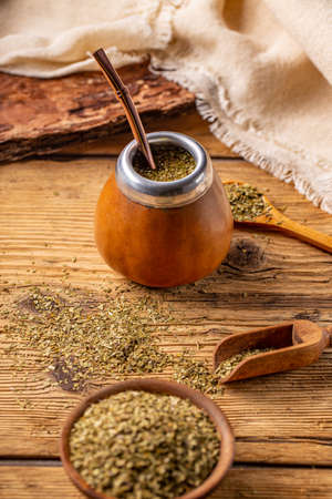Yerba mate leaves and tea mate in calabash with bombilla on a wooden background