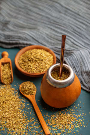 Pile of mate tea leaves and mate tea drink served in calabash gourd with bombilla