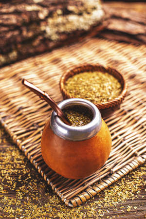 Mate tea in calabash with bombilla on bamboo tray