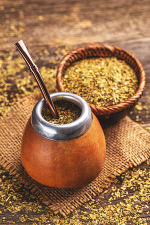 South American yerba mate tea in calabash with bombilla and dried leaves in wooden bowl