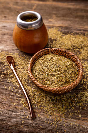 Yerba mate leaves in wooden bowl on wooden background
