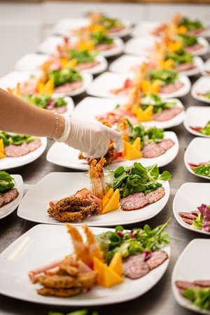 Many plates of appetizer being prepared in restaurant kitchen Stock Photo