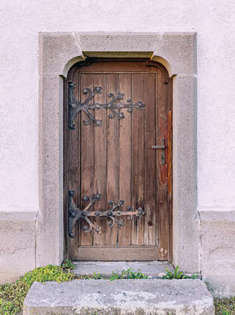 Weathered, old brown wooden door in an church building