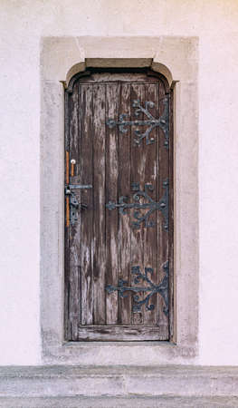 Ancient closed wooden door with wrought-iron hinges