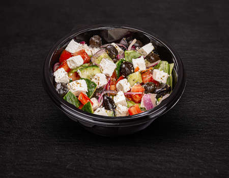 Tasty greek salad with feta, olives and tomatoes in a plastic bowl