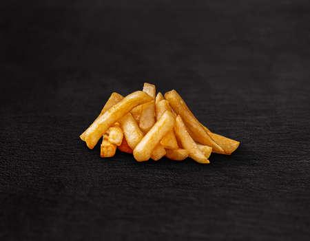 Heap of tasty french fries on dark background