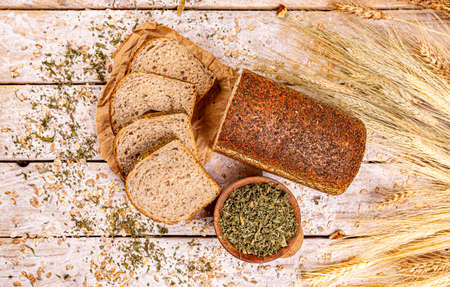 Flat lay of loaf of bread with dried basil on wooden background