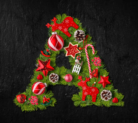 Letter A made of Christmas tree ornaments on a black slate background
