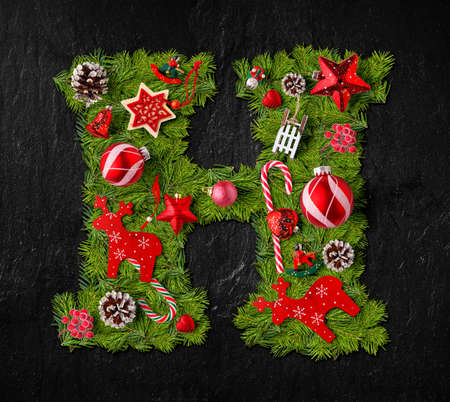 Letter H made of Christmas tree ornaments on a black slate background