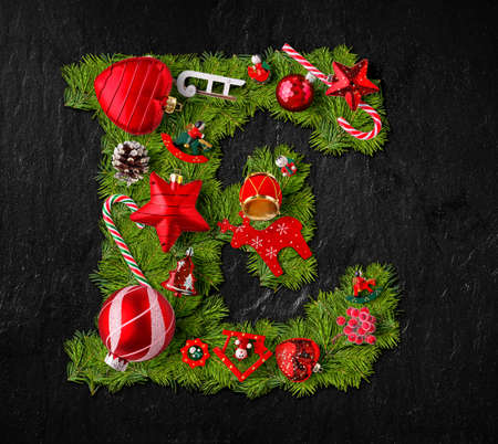Letter E made of Christmas tree ornaments on a black slate background