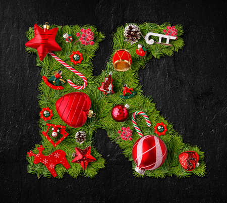 Letter K made of Christmas tree ornaments on a black slate background Stock Photo