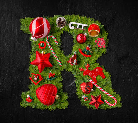Letter R made of Christmas tree ornaments on a black slate background Imagens