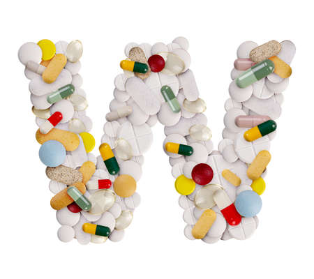 Capital letter W made of various colorful pills, capsules and tablets on isolated white background