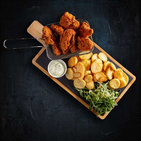 Flat lay of crispy fried chicken strips with golden potatoes and garlic sauce on dark background