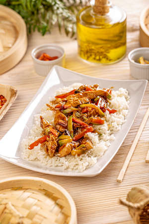 Stir frying chicken with vegetables garniched with white boiled rice