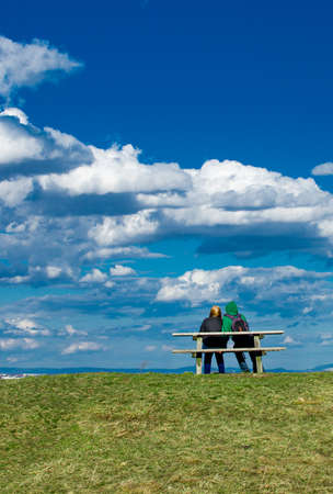 young couple outdoor on a bench Stock Photo