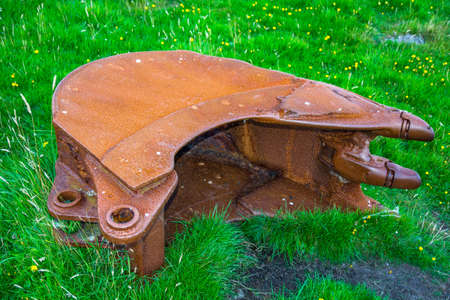 Old rusty excavator shovel in the grass photo
