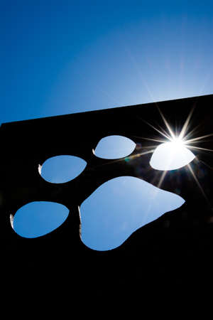 Silhouette of a cat paw with bright sunlight photo