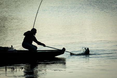 Pescatore cattura di pesce su un lago di Twilight