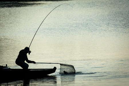 Fisherman Catching Fish on a Twilight Lake Stock Photo
