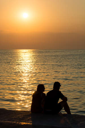 2 people: Young Couple on Beach at Sunset Stock Photo