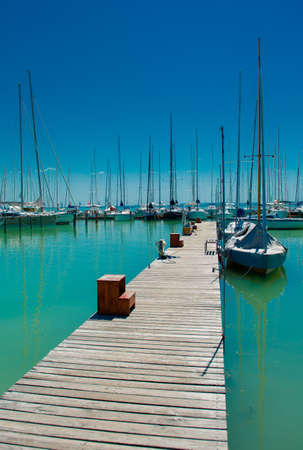 A long jetty of a harbor with numerous sail boats on Lake Balaton in Hungary