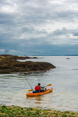 Man in paddle boat on beach in Ireland Stock Photo